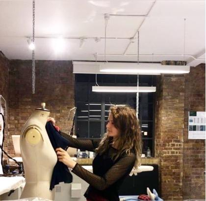 Zanna holds material to a dress form to provide continued sustainability in fashion.